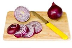 Cebollas rojas y un cuchillo. Foto de archivo
