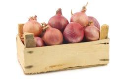 Cebollas rosadas en un cajón de madera Foto de archivo