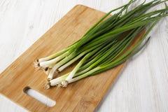 Cebollas verdes frescas en un tablero de bambú en un fondo de madera blanco, opinión de ángulo bajo Primer imagenes de archivo
