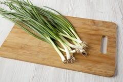 Cebollas verdes frescas en un tablero de bambú en una superficie de madera blanca, opinión de ángulo bajo Primer imagenes de archivo