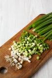 Cebollas verdes tajadas en un tablero de madera rústico sobre el fondo de madera blanco, opinión de ángulo bajo Primer foto de archivo
