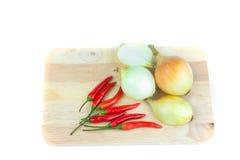 Cebollas y chiles en la tajadera Imágenes de archivo libres de regalías