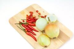 Cebollas y chiles en la tajadera Imagen de archivo