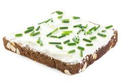 Cebolletas frescas del corte en el queso cremoso grueso separado en el pan oscuro de la salud Imagenes de archivo