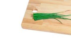 Cebolletas verdes en la tajadera de madera Fotografía de archivo