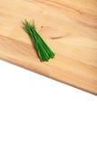 Cebolletas verdes en la tajadera de madera Foto de archivo