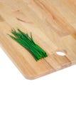 Cebolletas verdes en la tajadera de madera Imagen de archivo