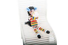 Cebra suave de los juguetes que se sienta en la silla fotografía de archivo libre de regalías