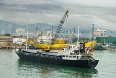 Cebu City Philippines from port. View of Cebu City (Southern Philippines) downtown seen from the sea with the port and a large worn bulk cargo ship in the Royalty Free Stock Photos