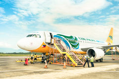Cebu Pacific aircfraft at Puerto Princesa airport. PUERTO PRINCESA, PHILIPPINES - 15 FEBRUARY, 2015: staff people moving around Cebu Pacific aircraft after stock image