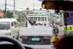 cebu Philippines - 19 octobre 2016 : L'homme dort dans le corps de camion sur la chaussée tandis que transport se déplaçant à l'h Image stock