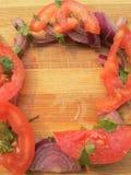 Cebuli i pomidoru kawałków rama na drewnianym tle Zdjęcia Stock
