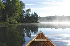 Cedar Canoe Bow på en Misty Lake Royaltyfria Bilder
