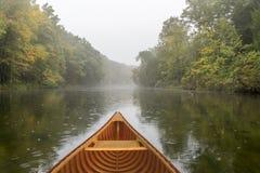 Cedar canoe on a river during a light rain royalty free stock photography