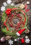 Cedar Christmas-Kranz mit Winterbeeren, Band und Feiertagsdekorationen auf rustikalem hölzernem Hintergrund Lizenzfreie Stockbilder