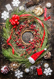 Cedar Christmas wreath with winter berries , ribbon and holiday decorations on rustic wooden background Royalty Free Stock Images
