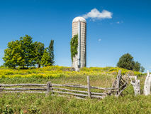 Cedar Fence Abandoned Farm Silo. In rural farm field country Stock Images