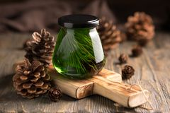 Cedar green honey in a jar on a boards with cedar cones on a simple wooden background. Jar of honey with pine cones. Stock Images
