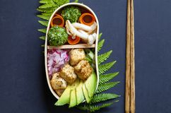 Japanese bento lunch box with tofu. Cedar Japanese bento box lunch with mushrooms, onigiri, avocado and tofu royalty free stock image