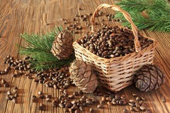 Cedar nuts in a wicker basket on a wooden table royalty free stock photography