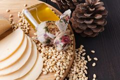 Cedar oil. Bottles with virgin cedar oil and pine nuts on the table royalty free stock photo