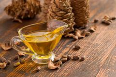 Cedar oil, nuts and cones On a wooden background. selective focus Royalty Free Stock Photos