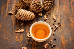 Cedar oil, nuts and cones On a wooden background. Top view Royalty Free Stock Photography