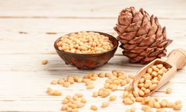 Cedar Pine nuts and cones on white wooden table Royalty Free Stock Images