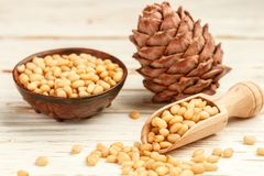 Cedar Pine nuts and cones on white wooden table Royalty Free Stock Image