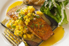 Cedar plank cooked salmon with mango salsa. And vegetables Royalty Free Stock Photos