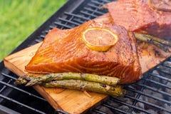 Cedar plank salmon with lemon on a grill Stock Image
