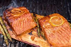Cedar plank salmon with lemon on a grill. Cedar plank salmon with lemon cooking on grill Royalty Free Stock Photo