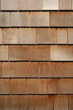 Cedar Shakes Background. Exterior Home Wall Covered in New Wooden Cedar Shakes or Shingles. Warm colors with nice details and textures Stock Image