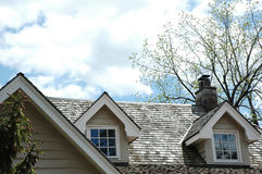Cedar Shingle Rooftop. Cedar shingle roof with chimney and cloudy blue sky background stock photography