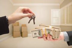 Cedendo o dinheiro para chaves da casa Fotos de Stock
