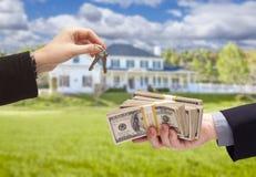 Cedendo o dinheiro para chaves da casa na frente da casa Fotografia de Stock