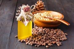 Cederkegel met noten en een glasfles met olie op een houten achtergrond De bron van natuurlijke vitaminen en mineralen Gebruikt i Stock Afbeeldingen