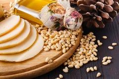 Cederkegel met noten en een glasfles met olie op een houten achtergrond De bron van natuurlijke vitaminen en mineralen Gebruikt i Royalty-vrije Stock Afbeeldingen