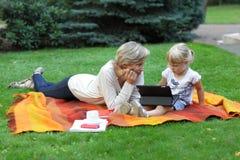 Cedo aprendendo - sira de mãe a olhar sua filha que usa a tabuleta foto de stock
