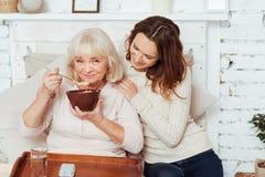 Ceerful elderly woman enjoying her breakfast. Stock Images
