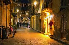 CEFALU, ITALY-JANUARY 03日2017年:古老狭窄的街道的圣诞灯装饰 人们走 库存照片
