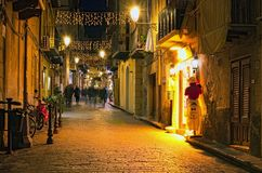 CEFALU, ITALY-JANUARY 03, 2017: Christmas lights decoration of ancient narrow street. People are walking Stock Photos