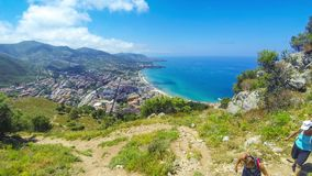 Panoramic aerial view of Cefalu city, Sicily, Italy. CEFALU, ITALY - MAY 14, 2018: People hike on hillside of Rocca di Cefalu, Sicily, Italy. Cefalu is one of stock video footage
