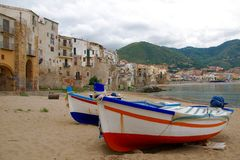 Cefalu Marina, Sicily. These fishing boats with their colorful lines against a backdrop of historical buildings led to my taking this photo of the Marina in Royalty Free Stock Photo