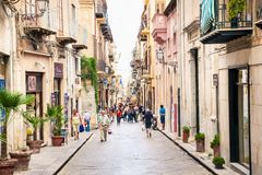 Old mediterranean steet with tourist in Cefalu, medieval city of. CEFALU, SICILY - SEPTEMBRE 16,2014: Old mediterranean steet with tourist in Cefalu, medieval Royalty Free Stock Photos