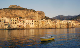 Cefalu town at sunset in Sicily. Scenic view of Cefalu town shoreline with boat in foreground sea, Sicily, Italy Royalty Free Stock Photography