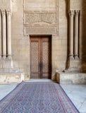 Cegły kamienna ściana z arabesk dekorującym drewnianym drzwi obramiającym kamiennymi ozdobnymi cylindrycznymi kolumnami, al Rifai obraz royalty free