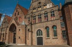 Ceglana fasada kościół, drewniany drzwi i niebieskie niebo w alleyway Bruges, Fotografia Stock