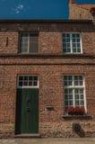 Ceglana fasada stary dom, kwiaty i błękitny pogodny niebo w pustej ulicie Bruges, Obraz Royalty Free