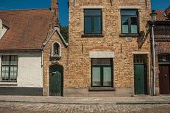 Ceglana fasada starzy domy i drzwi z niebieskim niebem, w pustej ulicie Bruges Fotografia Royalty Free